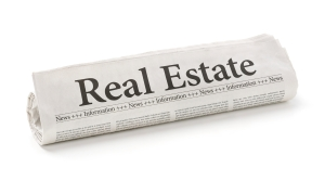 Rolled newspaper with the headline Real Estate
